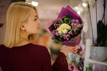 Female with flower bouquet in purple paper