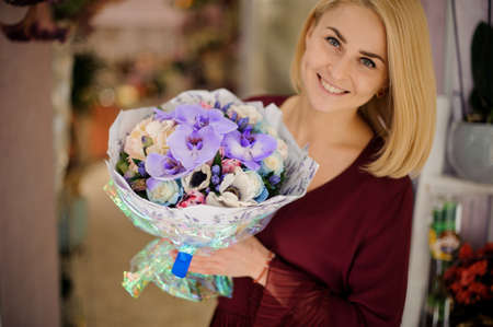 Smiling girl with lush bouquet with irises