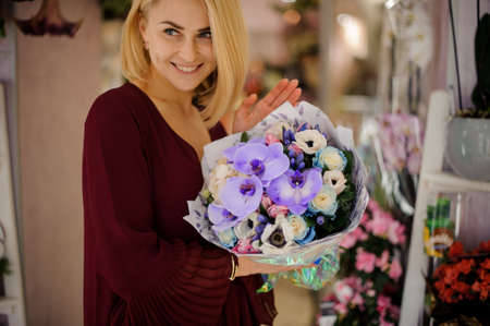 Smiling woman with lush bouquet with irises Stock fotó
