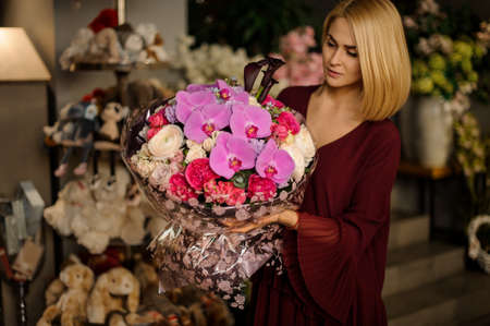 Well dressed girl looking at flower bouquet Stock fotó