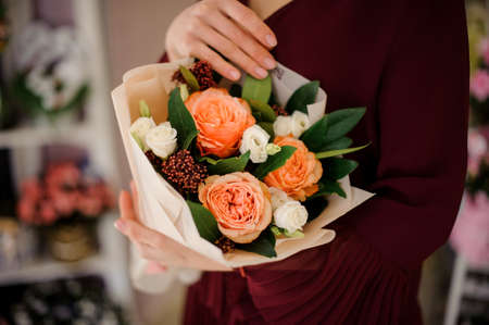 Close-up of amazing bouquet of peach roses in young woman's hands