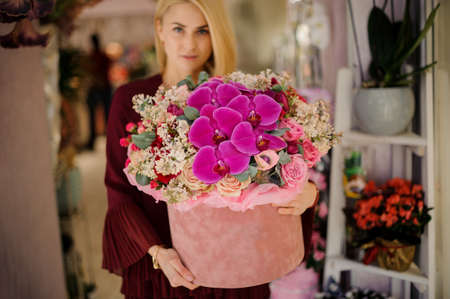 Blond girl standing with giant bouquet in box Archivio Fotografico - 138554632