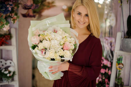 Smiling female in dress with flower bouquet Archivio Fotografico - 138554660