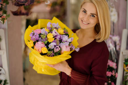 Smiling girl posing with colorful flower bouquet