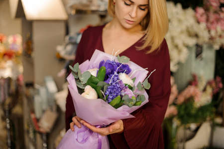 Woman in red dress looking at purple bouquet