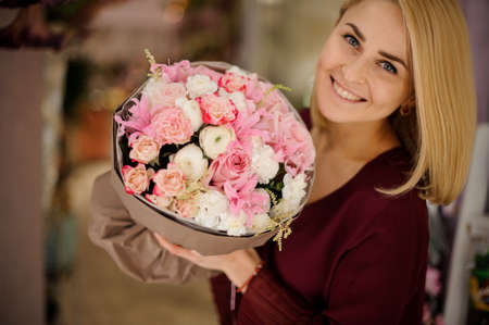 Smiling girl with lush bouquet of pink flowers