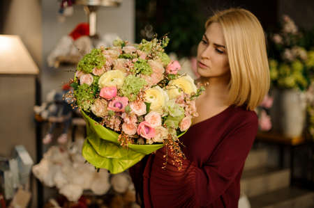 Well dressed woman looking at flower bouquet Archivio Fotografico - 138555054