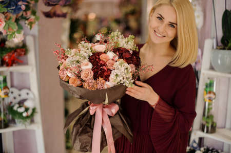 Happy girl holding rich and lush bouquet Archivio Fotografico - 138555144