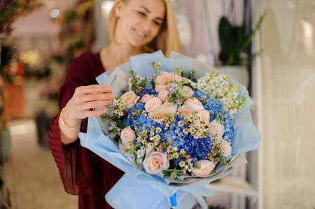 Cute girl with blue bouquet in hands