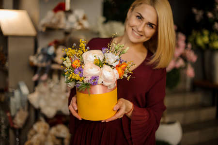 Blonde holds hat box with roses and wildflowers
