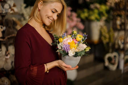Blonde holding small bouquet in textured pot