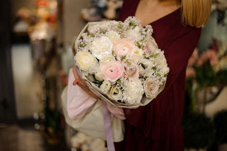 Close shot of amazing and lush holiday bouquet in womans hands