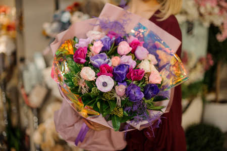 Close-up of amazingly beautiful bouquet of colorful flowers in women's hands Фото со стока