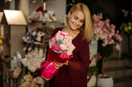 Attractive blond woman holds bouquet of flowers Stock fotó