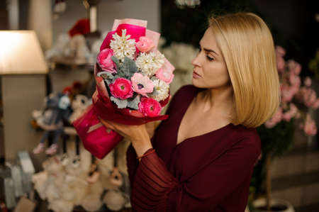 Attractive blond girl holds bouquet of flowers