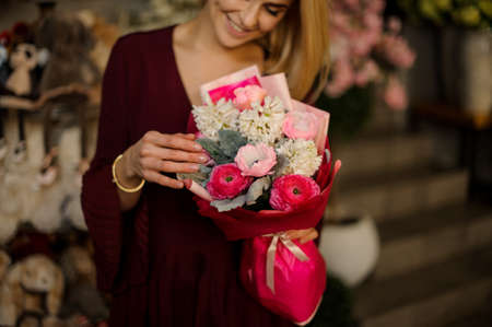 Smiling blond woman holds bouquet of flowers Stock fotó