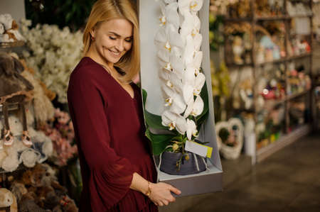 Beautiful woman holding giant flower in pot
