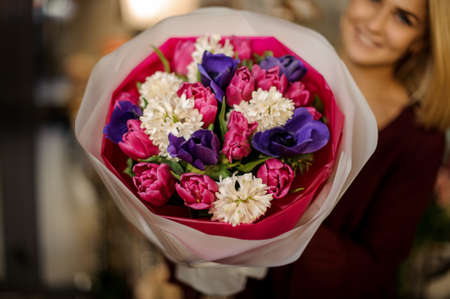 Close-up of blonde with bouquet of peonies and bellflowers
