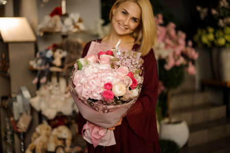 Blonde poses with bouquet of irises and roses Stock fotó