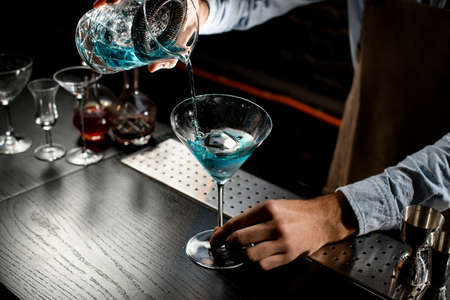 Bartender pouring a blue color alcoholic cocktail from the measuring cup with strainer to a martini glass on the bar counter