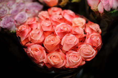Beautiful bouquet of bright peach color roses in the transparent wrapping paper in the blurred background in the flower shop
