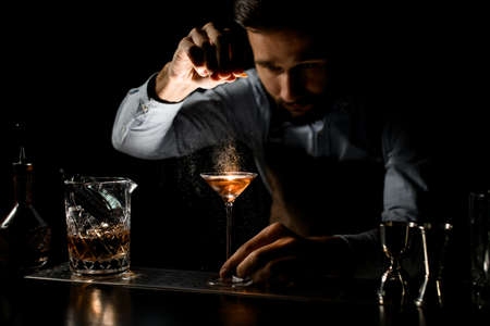 Bartender spraying on the alcoholic drink in a martini glass with orage zest juice on the bar counter