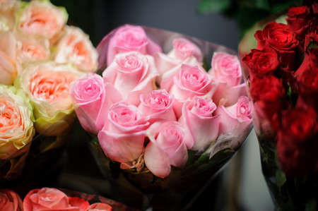 Beautiful bouquet of pink roses in the transparent wrapping paper in the blurred background in the flower shop