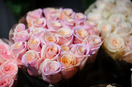 Beautiful bouquet of rosy peach roses in the transparent wrapping paper