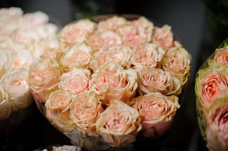 Beautiful bouquet of tender peach color roses in the transparent wrapping paper in the blurred background in the flower shop