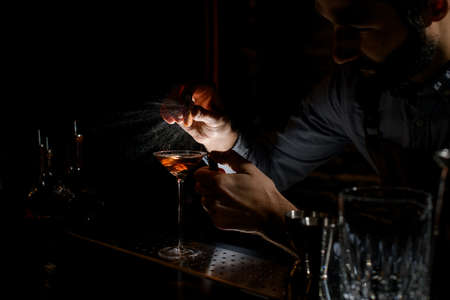 Bartender spraying on the alcoholic drink in a martini glass with orage zest juice in the dark