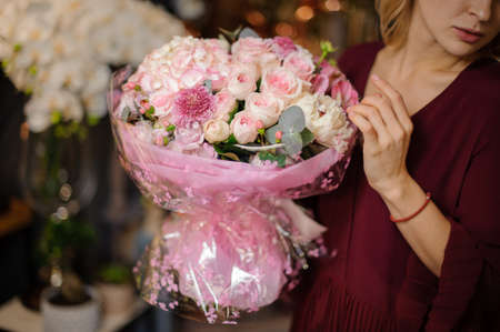 Girl holding a spring bouquet of tender rosy color roses in the wrapping paper in the blurred background of flower shop