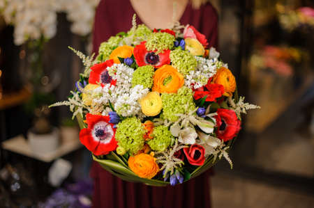 Girl holding a spring bouquet of white, green, orange and red flowers in the wrapping paper in the blurred background of flower shop