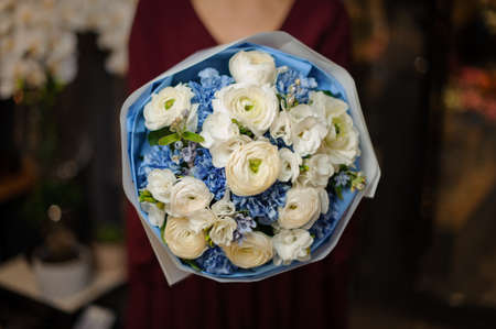 Woman holding a spring bouquet of tender white color roses and blue carnations in the wrapping paper in the blurred background of flower shop