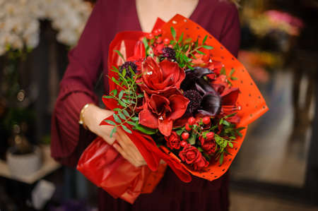 Girl holding a bouquet of bright red amaryllis with leaves and berries in the wrapping paper in the blurred background of flower shop Stock fotó