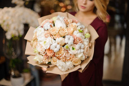 Girl holding a spring bouquet of tender white carnation and creamy roses decorated with cotton in the wrapping paper Stock fotó