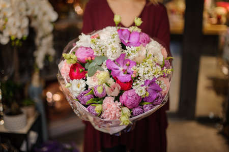 Girl holding a spring bouquet of tender pink, white, red and violet flowers in the wrapping paper in the blurred background of flower shop Stock fotó