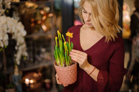 Girl holding a little peach color pot with a green Narcissus with yellow flowers