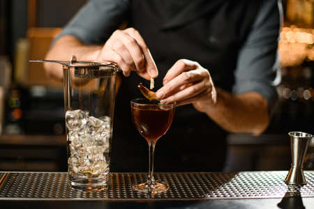 Professional bartender decorating a brown cocktail in the glass with a dried leaf by a pin on the bar counter