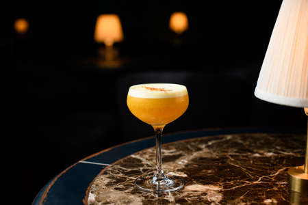 Orange alcoholic cocktail with a white scum decorated with orange zest on the marble table under the light