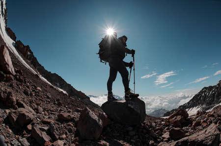 Homme debout sur le rocher autour des restes de neige sous le soleil dans un ciel clair Banque d'images