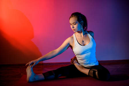 Girl in sport clothes practicing yoga in a studio room stretching her legs Banco de Imagens
