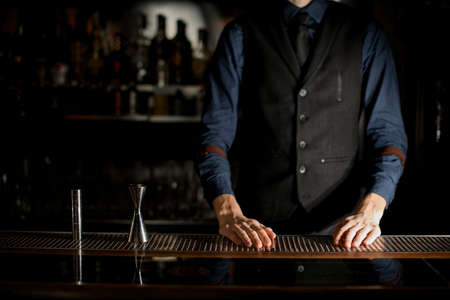 Bartender in blue shirt is standing behind the bar. Stockfoto