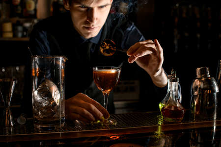 Young barman decorates glass with cocktail by burnt citrus slice. Stockfoto