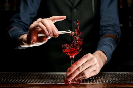 Professional bartender's hand carefully decorated splashing red alcoholic drink in glass by small rose flower.