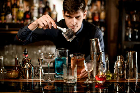 bartender holds by forceps big ice cube over a glass at the bar. Stock Photo
