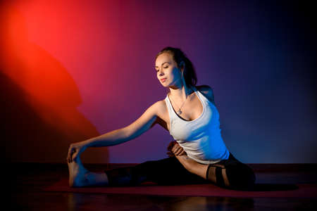 Beauty girl in the studio sits on special red mat in yoga pose.