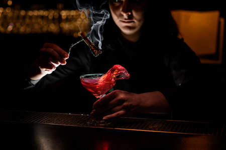 bartender girl holds smoking wand and glass with red splashing drink.