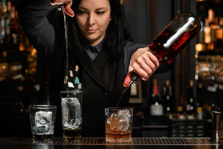 bartender girl holds bottles with drink and professional pours it into glass with ice.