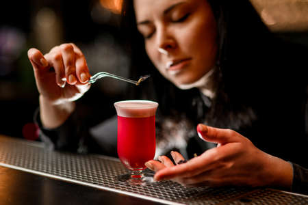 Bartender carefully hold tweezer with flower over cocktail glass.