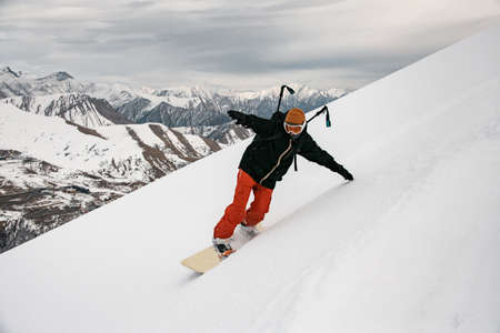 man snowboarder in bright clothes moving down the mountain. Cloudy sky and snow-capped mountains in background.